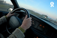 Mature woman driving car, close-up of hands, dusk (Licence this image exclusively with Getty: http://www.gettyimages.com/detail/200502965-001 )