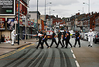 Police search the scene where 21 year old Haroon Jahan, and brothers Shazad Ali (30) and Abdul Musavir (31) were killed on Tuesday evening in a hit and run incident by suspected looters as they guarded a petrol station forecourt with many other people on Dudley Road in the Winson Green area of Birmingham, which was hit by a surge of rioting and looting. The violence started in London on Saturday evening after a peaceful protest in response to the shooting by police of Mark Duggan during an attempted arrest escalated into a riot, but has now spread to other areas in the country.