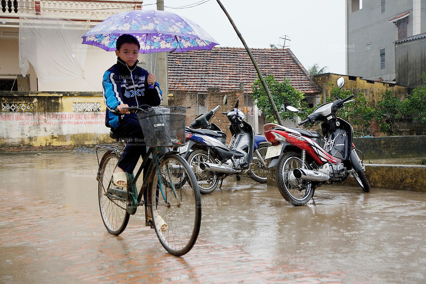 Vietnam. Ha Tay province. Lai Xa. On a rainy sunday afternoon, a young boy rides his bicycle while protecting himself with an umbrella. Lai Xa is a typical hamlet (village) and is part of the Kim Chung commune located 15 km west of Hanoi. 05.04.09 © 2009 Didier Ruef
