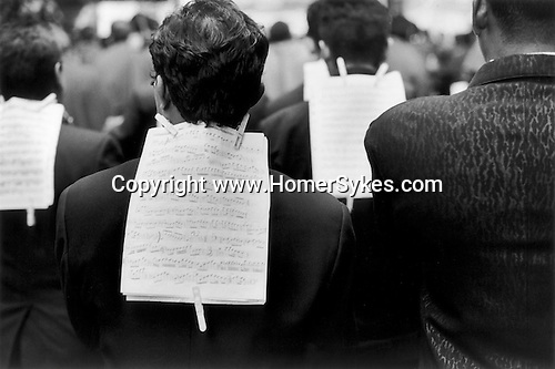 New York, 1999. A Saints Day procession procession through the streets of Manhattan. The ethnic musicians down a midtown street, the sheets of music are attached to the back of the musician in front with cloths pegs. 1990s.