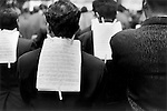 New York, 1999. A Saints Day procession procession through the streets of Manhattan. The ethnic musicians down a midtown street, the sheets of music are attached to the back of the musician in front with clothes pegs. 1990s.