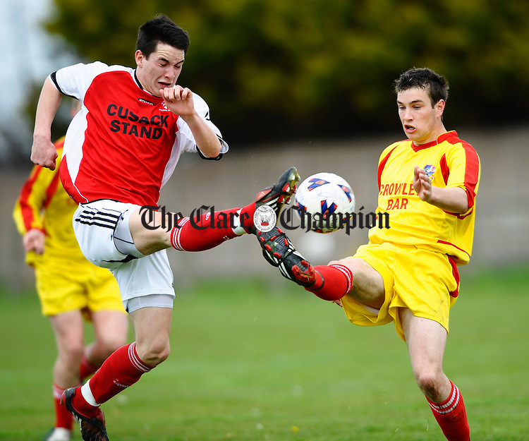Newmarket's Alan Casey kicks past the foot of Corofin's Damian Ryan  during the Youths Cup final at Doora. Photograph by John Kelly.