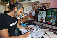 """Switzerland. Canton Ticino. Bruzella. Ivan Artucovich, AKA Ivan Art, is a graphic illustrator and a cartoonist. He is the co-owner of the """"Why Not"""" shop, located in Chiasso, which sells various cannabis CBD and hemp products. For years, Ivan Art has been creating awareness and shedding new light on the multiple uses of cannabis with the goal to make society rethinking about its preconceptions towards the magnificent plant. He started publishing his series of comics strips in 2006 and since then has made his way to numerous international publications. On his iMac, some comic strips from  the """" Why? Why not? """" project and a drawing from Helvetia smelling cannabis while wearing a cannabis wreath on her head. Helvetia is the female national personification of Switzerland, officially the Swiss Confederation. The allegory is typically pictured in a flowing gown with a shield emblazoned with the Swiss flag, and commonly with braided hair and a wreath as a symbol of confederation. The flag of Switzerland consists of a red flag with a white cross (a bold, equilateral cross) in the centre. It is one of only two square sovereign-state flags. The business of selling cannabis CBD is registered with the Swiss Federal Health Office. The Swiss legal requirements have a 1 percent THC limit compare to the European Union (EU) where the THC limit is limited to 0.3 percent. Cannabidiol (CBD) is a phytocannabinoid discovered in 1940. It is one of some 113 identified cannabinoids in cannabis plants and accounts for up to 40% of the plant's extract. Cannabidiol can be taken into the body in multiple ways, including by inhalation of cannabis smoke or vapor, as an aerosol spray into the cheek, and by mouth. It may be supplied as CBD oil containing only CBD as the active ingredient (no included tetrahydrocannabinol [THC] or terpenes), a full-plant CBD-dominant hemp extract oil, capsules, dried cannabis, or as a prescription liquid solution. 16.09.2019 © 2019 Didier Ruef"""