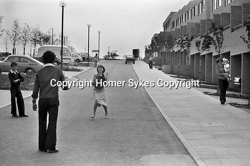 1970s children playing in the street very few cars in a modern new middle income housing development, a new town is being built. 1977 England Milton Keynes Buckinghamshire.