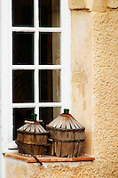 On a window sill in the courtyard, two old demi-johns. Chateau Mourgues du Gres Grès, Costieres de Nimes, Bouches du Rhone, Provence, France, Europe