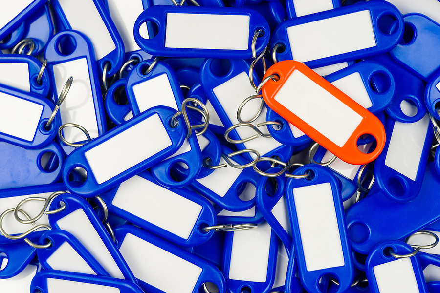 many blue and a single orange plastic key tag