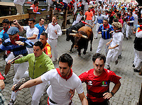 Participants run in front of Cebada Gago bulls during the third bull run of the San Fermin festival, on July 9, 2012, in the Northern Spanish city of Pamplona. The festival is a symbol of Spanish culture that attracts thousands of tourists to watch the bull runs despite heavy condemnation from animal rights groups. (c) Pedro ARMESTRE