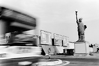 France. Pyrénées-Orientales department. Perpignan. A replica of the Statue of Liberty (3.5 m height). Public bus blurred on road. 6.09.05 © 2005 Didier Ruef