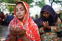 Mother of a missing garments worker prays at Adhad Chandra High School.