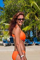 Honduras, Roatan Island, Fantasy Island Resort, Caribbean. Woman (Sam) walking on the beach with palm trees.