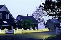 USA, Maine, Camden,homes, street and picket fence illuminated at dawn