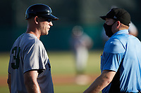 Augusta GreenJackets manager Michael Saunders (38) argues with home plate umpire Jacob McConnell during the game against the Charleston RiverDogs at Joseph P. Riley, Jr. Park on June 27, 2021 in Charleston, South Carolina. (Brian Westerholt/Four Seam Images)