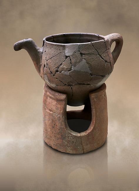 Hittite terra cotta teapot with strainer spout on a charcoa; burner base  . Hittite Period, 1600 - 1200 BC.  Hattusa Boğazkale. Çorum Archaeological Museum, Corum, Turkey. Against a warm art bacground.