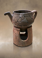Hittite terra cotta teapot with strainer spout on a charcoa; burner base  . Hittite Period, 1600 - 1200 BC.  Hattusa Boğazkale. Çorum Archaeological Museum, Corum, Turkey. Against a warm art bacground.