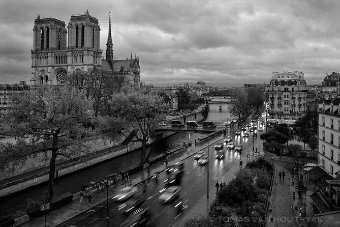 Rush hour traffic fills the Quai de Montebello, while gendarme (police) trucks wait on the Pont au Double bridge leading across the Seine river to Notre Dame Cathedral in Paris, France, four days after coordinated terrorist attacks struck the heart of the French capital.