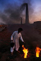 A worker at a brick factory with smoke stacks of the industry belching out black dirty smoke into the air.<br /> <br /> Just outside the Harappa site they are making bricks the same way the ancient Harappans did, by burying clay bricks and burning rice husks for fuel to fire the bricks.