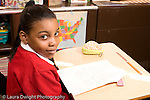 K-8 Parochial School Bronx New York Grade 4 portrait of girl looking up from reading in class horizontal