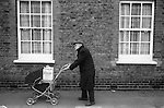 Old age pensioner pushing shopping home in a pram. He is wearing his slippers outside. Groceries are in  the two cardboard boxes. Battersea London UK 1970s.