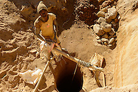 MADAGASCAR, region Manajary, town Vohilava, small scale gold mining / MADAGASKAR Mananjary, Vohilava, kleingewerblicher Goldabbau, Goldsucher foerdern Steine und Sand aus einem Stollen, die am Fluss nach Gold gewaschen werden