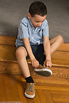 4 year old boy dressing self putting on own shoes