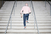 A man walks up stairs at the Democratic National Convention at the Wells Fargo Center in Philadelphia, Pennsylvania, on Wed., July 27, 2016.  There are few elevators in the Wells Fargo Center with long waits, so many people opt to use the stairs.