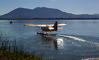 A Stinson 108-3 on floats, N6826M, taxis for take off at the Clear Lake Seaplane Splash-In, Lakeport, Lake County, California; in the middle ground a trike on floats taxis by, Mount Konocti is in the background