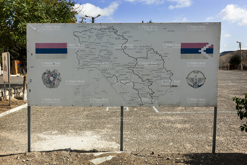 """Nagorno-Karabakh, also known as Artsakh, is a landlocked region in the South Caucasus. Madaghis is a village in the Martakert region of the Nagorno-Karabakh Republic (de facto) and in the Tartar District of Azerbaijan (de jure). It has been under Armenian control since April 1994. Army base. Military barracks. A map from Armenia and Nagorno-Karabakh. The national flag (L) of Armenia, the Armenian Tricolour, consists of three horizontal bands of equal width, red on the top, blue in the middle, and orange (also described as """"colour of apricot"""") on the bottom. The Armenian Supreme Soviet adopted the current flag on 24 August 1990. On 15 June 2006, the Law on the National Flag of Armenia, governing its usage, was passed by the National Assembly of Armenia. On June 2, 1992, the self-proclaimed Republic of Artsakh adopted a flag (R) derived from the flag of Armenia, with only a white pattern added. A white, five-toothed, stepped pattern was added to the flag, beginning at the two verges of the flag's right side and meeting at a point equal to one-third of the distance from that side. The white pattern symbolizes the current separation of Artsakh from Armenia proper and its aspiration for eventual union with """"the Motherland."""" This symbolizes the Armenian heritage, culture and population of the area, and represents Artsakh as a separated region of Armenia by the triangular shape and the zigzag cutting through the flag. The white pattern on the flag is also similar to the designs used on rugs, a symbol of national identity. Nagorno-Karabakh is a disputed territory, internationally recognized as part of Azerbaijan, but most of the region is governed by the Republic of Artsakh (formerly named Nagorno-Karabakh Republic), a de facto independent state with Armenian ethnic population.  Since 1994, regular peace talks between Armenia and Azerbaijan mediated by the OSCE Minsk Group have failed to result in a peace treaty. 8.10.2019 © 2019 Didier Ruef"""