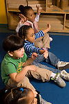 Preschool 3 year olds singing song with hand gestures at circle time