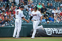 Charlotte Hornets manager Mark Grudzielanek (15) slaps hands with Daniel Palka (7) as he rounds third base after hitting a home run against the Louisville Bats at BB&T BallPark on June 22, 2019 in Charlotte, North Carolina. The Hornets defeated the Bats 7-6. (Brian Westerholt/Four Seam Images)