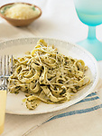 A plate of fettuccine pasta, dressed with pesto and topped with parmesean.