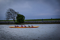 A slow shutter capture blurs the rowing team in motion on the waters of San Francisco Bay.
