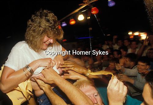 Mildenhall, Suffolk. 1980's<br /> Getting out of hand, a wet T-shirt contestant get carried shoulder high along the temporary stage outside the Bird in Hand pub. Organised by a local entrepreneur cashing in on the serviceman's US dollars pay packets and their single status.