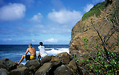 Big Island, Hawaii. Young couple sitting on rocks at Keokea Beach Park looking out to sea.