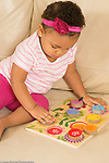 18 month old toddler girl at home playing with puzzle