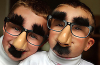 Two boys make each other laugh by wearing funny glasses.