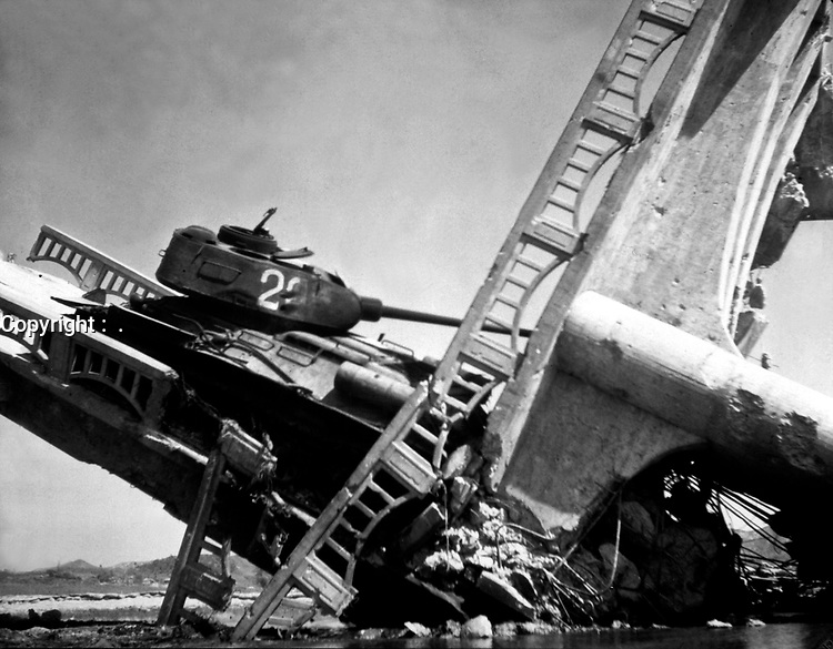 The wreckage of a bridge and North Korean Communist tank south of Suwon, Korea.  The tank was caught on a bridge and put out of action by the Air Force.  October 7, 1950. Marks. (Army)<br /> NARA FILE #:  111-C-6143<br /> WAR & CONFLICT BOOK #:  1499