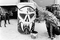 """Italy. Province of Emiglia Romagna. Santarcangelo di Romagna. Mutoid Waste Company. A woman with tatoes on both arms paints the drums which will be used for the next show at """"Inycon"""" festival in Menfi, Sicily. Using all types of industrial scrap for their raw materials the Mutoid Waste Company are a mobile and adaptable group of performance artists. Having the necessary equipment to allow them complete freedom, they have created an entirely new form of scultural-musical performance crossing the boundaries of circus, theatre and art. © 1999 Didier Ruef"""