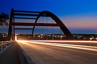 Cars leave light trails as the pass through the Loop 360 Pennybacker Bridge in Austin, Texas