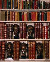 A collection of bronze heads acts as book ends on shelves in the library at Hambledon
