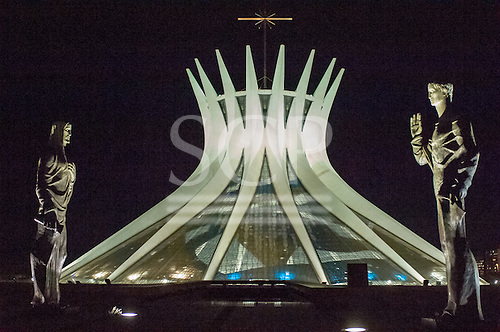 Brasilia, DF, Brazil. The Metropolitan Cathedral of Nossa Senhora Aparecida at night with statues of the evangelists guarding the entrance.
