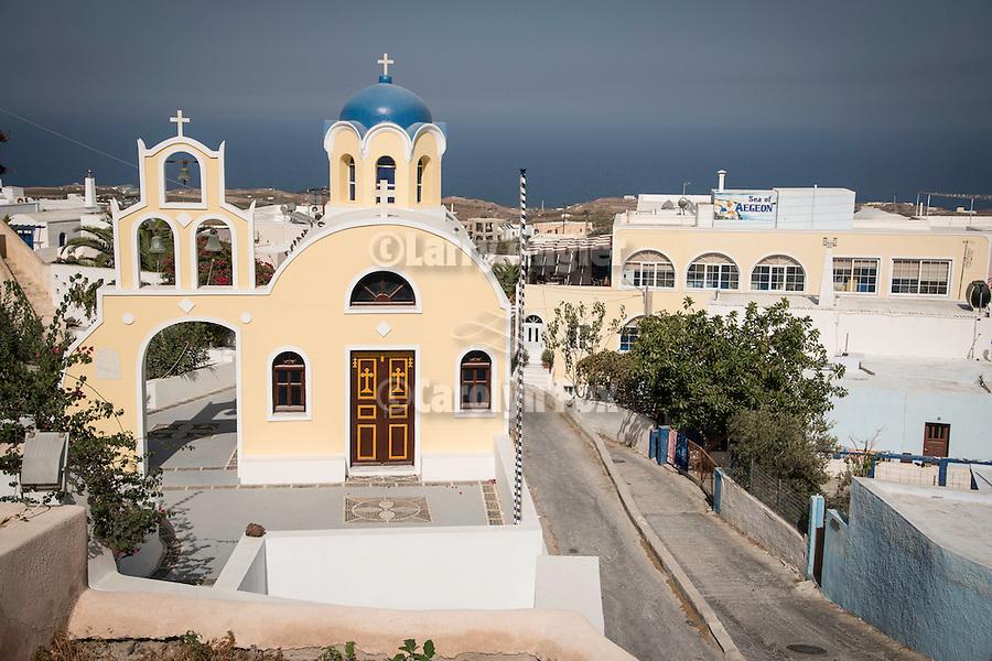 A blue-domed, pale yellow Greek Orthodox church, Fira, Santorini, Greece.
