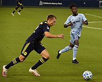 KANSAS CITY, KS - OCTOBER 11: #12 Gerso Fernandes of Sporting Kansas City tries to position himself in the way of #12 Alistair Johnston of Nashville SC as he drives the ball upfield during a game between Nashville SC and Sporting Kansas City at Children's Mercy Park on October 11, 2020 in Kansas City, Kansas.