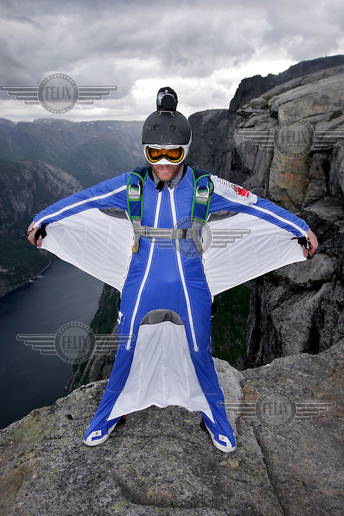 """Hans Holmefjord spreading his wings on a mountain top. Kjerag in the Lysebotn fjord is popular with BASEjumpers, but considered fairly unchallanging by the wingsuit flyers of """"Verdal'n BASE and Karsk"""". © Fredrik Naumann"""