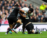 Billy Vunipola of England is stopped by Keven Mealamu (left) and Sam Whitelock of New Zealand during the QBE Autumn International match between England and New Zealand at Twickenham on Saturday 16th November 2013 (Photo by Rob Munro)
