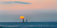 The sun sets on the famous Waikiki Beach of Oahu, Hawaii as two sail boats pass by.
