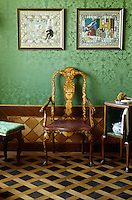 A Dutch marquetry armchair in the bathroom, above which hang two Russian embroideries against the green damask wall