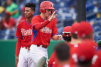GCL Phillies center fielder Mickey Moniak (15) high fives teammates after scoring a run during a game against the GCL Blue Jays on August 16, 2016 at Bright House Field in Clearwater, Florida.  Daniel Brito is behind Moniak.  GCL Blue Jays defeated GCL Phillies 2-1.  (Mike Janes/Four Seam Images)