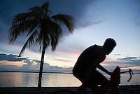 Man cycling along the waterfront at sunset, Cienfuegos, Cuba.