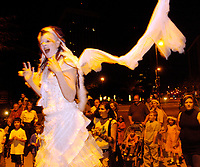 Walking on stilts, Anastazia Louise (CQed), of the Carpetbag Brigade, take part in the Parade of Little Angels Saturday night. The event was part of All Souls Procession festivities and took place at the downtown main library, 100 North Stone Ave.