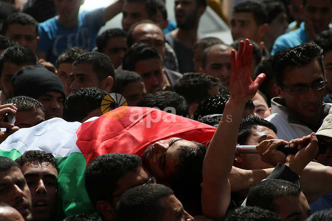 Palestinians carry the body of Mahmoud Adel al-Titi, 22, during his funeral in the West Bank refugee camp of al-Fawwar near Hebron 13 March 2013. Al-Titi was allegedly shot dead by an Israeli soldier during an Israeli military operation in al-Fawwar refugee camp on Tuesday. Photo by Mamoun Wazwaz